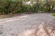 View of sandy site nineteen showing live oak trees, picnic table, fire ring and wooden railings under shady maritime hammock in Anastasia State Park.