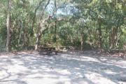 Side view of sandy site 32 showing picnic table, wooden railings, lantern post and live oak trees nestled under shady maritime hammock in Anastasia State Park.