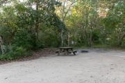 Side view of sandy site 93 showing picnic table, fire ring and wooden railing with live oak trees nestled under shady maritime hammock in Anastasia  State Park.