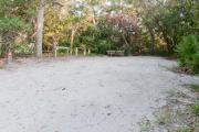 Side view of sandy site 101 showing picnic table, lantern post and wooden railing with live oak trees nestled under shady maritime hammock in Anastasia State Park.