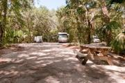 Rear view of sandy site 112 showing picnic table nestled under the shady live oak trees and maritime hammock in Anastasia State Park.