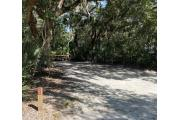 Rear view of sandy site 122 showing picnic table and fire ring nestled under the shady live oak trees and maritime hammock in Anastasia State Park.