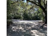 Side view of sandy site 122 showing picnic table with live oak trees nestled under shady maritime hammock in Anastasia State Park.