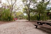 Rear view of sandy site 132 showing picnic table nestled under the shady live oak trees and maritime hammock in Anastasia State Park.