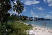 Photo: BAHIA HONDA SP. A white sandy beach with coconut palms, the Old Bahia Honda Bridge is in the background and people are wading in the blue-green water.