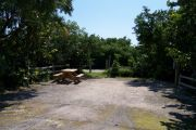 Photo: Buttonwood: Small, gravel, partially shaded campsite with picnic table and grill, bordered by a wood fence and surrounded by bushes.