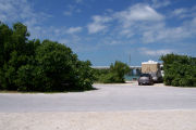 Photo: Buttonwood: Paved road with a campsite on the other side, bushes border site, water and new Bahia Honda Bridge in the background.