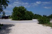 Photo: Buttonwood: Paved cul-de-sac with bushes in the middle, campsite on the left with silver camper, bushes border sites, new Bahia Honda Bridge in the background.