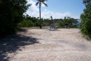 Photo: Buttonwood: Gravel campsite with picnic table, surrounded by bushes. Water and old Bahia Honda bridge in the background.