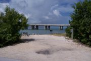 Photo: Buttonwood: Gravel site with picnic table and grill, bushes, water and new Bahia Honda Bridge in the background.