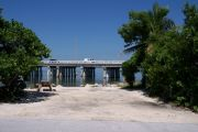 Photo: Buttonwood: Gravel site with picnic table and grill, bushes on either side, water and new Bahia Honda Bridge in the background.