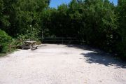 Photo: Buttonwood: Partially shaded gravel campsite with picnic table and grill, bordered by a wood fence and surrounded by bushes and palms.