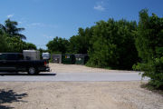 Photo: Buttonwood: Paved road with small gravel parking lot across road, dumpsters and vehicles in back ground.