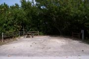 Photo: Buttonwood: Sunny gravel campsite with picnic table and grill bordered by a wood fence and surrounded by bushes.