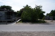 Photo: Buttonwood: Paved road with small gravel parking lot and bathhouse across road, bushes in back ground.