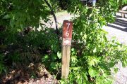 Photo: 076, BAYSIDE: Site number post with white number and arrow on a brown background, bushes in background.