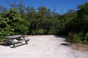 Photo: 078, BAYSIDE: Small gravel campsite with picnic table and grill, surrounded by trees.