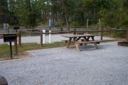View of a picnic table, fire ring and fence in bright sunshine.