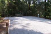 A view of the campsite with a shell/sand base and partial shade.