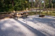 View of a picnic table, fire ring and clothesline posts in partial shade.