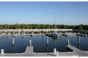 The photograph shows a view of boat slips in the Caladesi Island marina. An aluminum floating dock features power and water pedestals, with an aluminum seawall and green palm trees in the background. Concrete pilings support the docks.  Finger docks protrude out from each side of the main dock at intervals of every two boat slips.