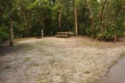 The wooden site marker is to the right. This site has sparse green grass and tan sandy soil. It's shaded and surrounded by green vegetation. The brown metal ground grill, gray electrical box, water spigot and a wooden picnic table are near the back, center to right.