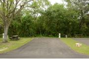 This photo shows the paved driveway with a wooden picnic table, gray electrical box, water spigot, a tree, and green vegetation towards the back of the site. This site has green grass and some tan soil.