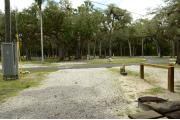 This view shows a wooden picnic table, brown ground grill, water spigot and gray electrical box to the left. The soil is gray to tan color. Green palms are in the background. A guide wire is to the left.