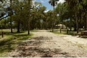 This view shows a wooden picnic table and brown ground grill center. A water spigot and a gray electrical box are in the background. The soil is gray to tan color. The grass is green. Green Cabbage Palms and Oak trees are in the background. This site is shaded.