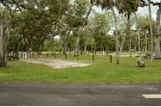 The site marker is to the left. Oak trees and Cabbage Palms scatter this site. A brown ground grill, gray utility box & wooden picnic table are to the right. The soil is gray sand & sparse green grass with scattered pine needles. A gray truck is to the right.