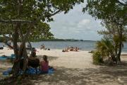 Photo: JOHN PENNEKAMP CORAL REEF SP. Park visitors swimming in waters of Largo Sound and sunbathing on blankets with coolers on sand at Cannon Beach with a few shade trees and historic cannons and in the background white clouds, blue sky and green tree-lined land