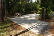 ADA-accessible pull-through campsite with concrete pad, picnic table and concrete sidewalk.