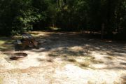 Deep campsite with picnic table and ground grill.