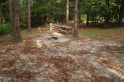 Campsite with picnic table and ground grill.