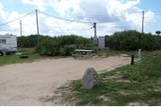 Packed sand campsite with no privacy vegetation between sites. Picnic table and ground grill located on the left. Barricade posts in back of site. Palmetto plants provide a thick buffer to the back. Electric and water hookups located to the right.