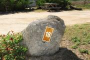 Large rock with metal sign with campsite number 18 on it located to the right of the site. Ground cover around rock.