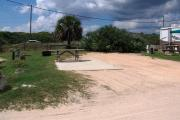 Packed sand campsite with large palmetto plants with palm tree. Low vegetation between sites. Handicap-accessible picnic table sits on a concrete pad and accessible ground grill off to the left of the campsite. Electric and water hookups on right side. Palmetto plants provide a buffer to the back.