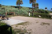 Packed sand campsite with palmetto plants along the back providing a buffer.  Handicap-accessible picnic table sits on a concrete pad. Barricade posts to protect vegetation. Electric and water hookups on right.