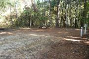 Campsite with picnic table and ground grill, electric and water hookups.