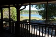 View from the porch of a modern ADA compliant cabin. This porch overlooks a beautiful blue lake.