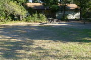 View of a vacant campsite with a picnic table, fire ring, and water spigot. The main area of the site is grassy with some sand and there are bushes on the edges of the site. There is partial shade. The campsite restroom is present in the background. This site does not have electricity.