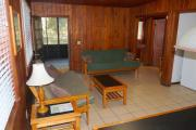 View of the inside of a block cabin. The living room has two futons, a coffee table, and a dining table. Just beyond the living room are the bedroom and bathroom. Also pictured is the screen porch off of the living room. The walls are wood and the floors are tile.