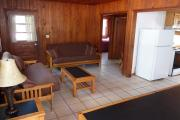 View of the inside of a block cabin. The living room has two futons, a coffee table, and a dining table. Just beyond the living room are the bedroom and bathroom. Also pictured is the kitchen. The walls are wood and the floors are tile.