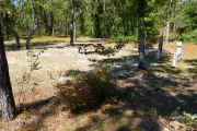 View of a vacant campsite with a fire ring, a picnic table, electric pedestal, and a water spigot. The vegetation is sparse and there are several trees on the edges of the site. A few small bushes are present in the foreground and there is partial shade in the site.