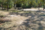 View of a vacant site showing a brown site marker with an arrow on a wooden post. The site is grassy with some patches of sand. There is a fire ring, picnic table, electric pedestal, and a water spigot. The site has partial shade and a few small trees in the center of the site.