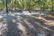 View of a vacant site with a picnic table, fire ring, electric pedestal, and a water spigot. The main part of the site is sandy with sparse vegetation. There are a few medium size trees in the center of the site and the site is well shaded.