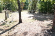 View of a vacant site with a picnic table, fire ring, electric pedestal, and a water spigot. Grass is present in most of the site and there is partial shade. The site has several small trees on the edges.