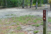 View of a vacant campsite with a brown site marker in the foreground. There is grass around the site marker but the main part of the site is sandy. Several trees are in the background and an electric pedestal and water spigot are on the back edge of the site.
