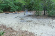View of a vacant campsite with a picnic table, fire ring, electric pedestal, and water spigot. The main part of the site is sandy. There are several trees surrounding the site and it is partly shaded.