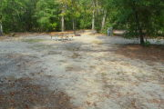 View of a vacant campsite with a picnic table, fire ring, electric pedestal, and water spigot. The site is sandy and has trees all around. There is partial shade.